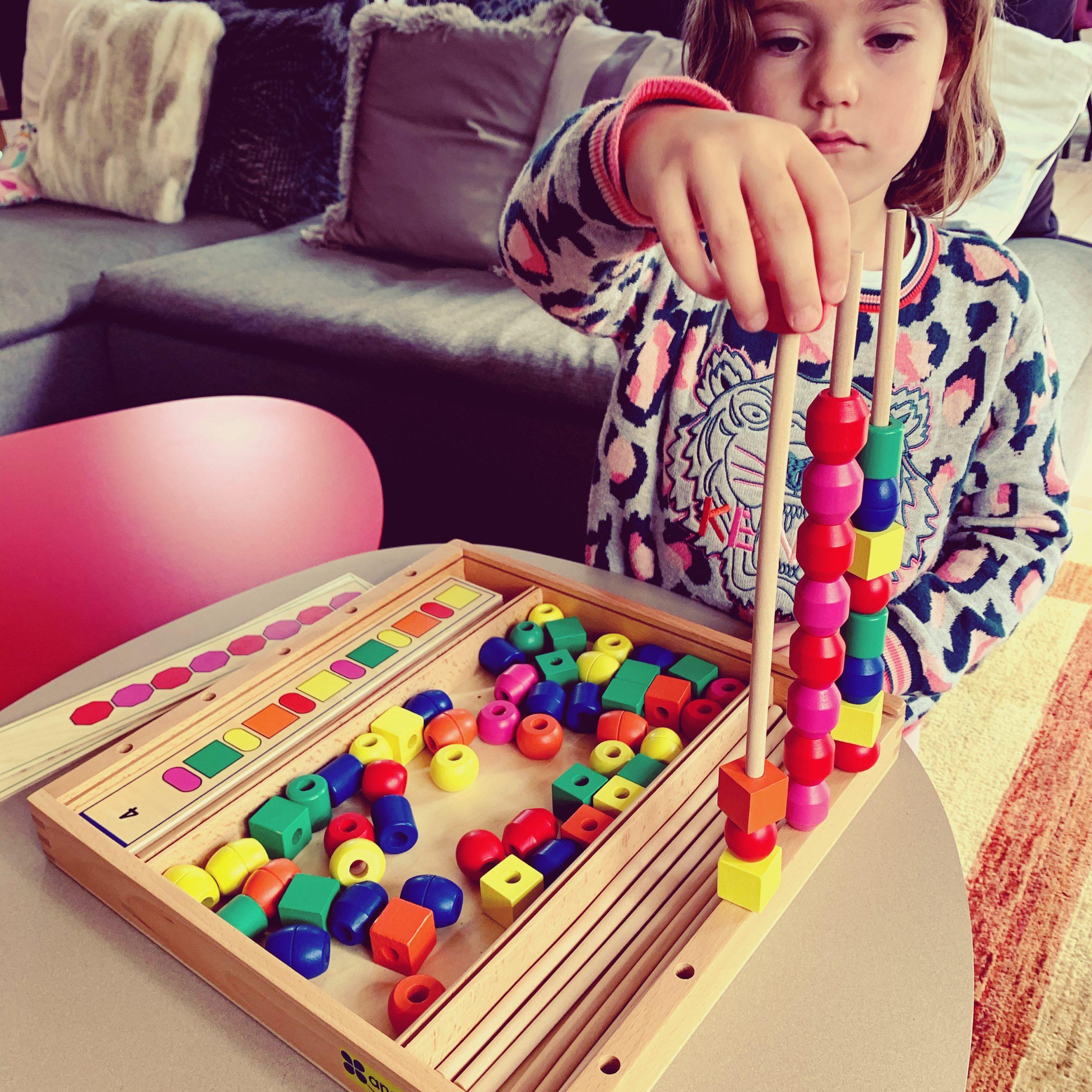 enfant jouant avec un jeu éducatif en bois